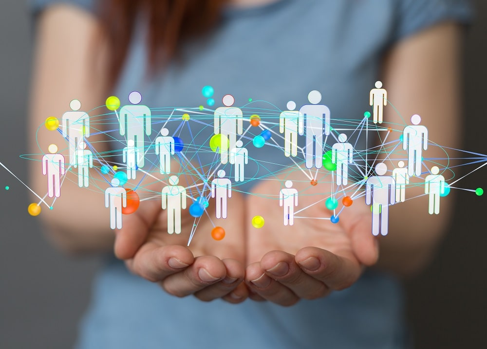 Un paire de main paumes vers le haut, présentant un image virtuelle de personnes reliées entres elles par des liens symbolisant le codéveloppement professionnel.